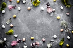 Easter background with mini candy eggs and speckled colorful fea. Ther on a dark background top view empty space for text Royalty Free Stock Images