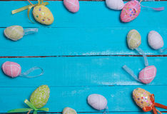 Easter background. Multicolored decorated easter eggs, multi-colored powder on a turquoise background. Free space. Easter background. Multicolored decorated Stock Photos