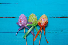 Easter background. Multicolored decorated easter eggs, multi-colored powder on a turquoise background. Free space. Easter background. Multicolored decorated Royalty Free Stock Image