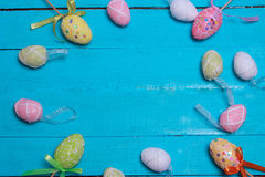 Easter background. Multicolored decorated easter eggs, multi-colored powder on a turquoise background. Free space Royalty Free Stock Images