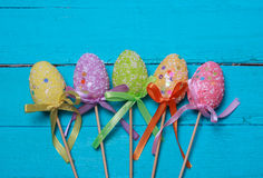 Easter background. Multicolored decorated easter eggs, multi-colored powder on a turquoise background. Free space. Easter background. Multicolored decorated Stock Image