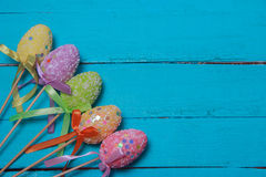 Easter background. Multicolored decorated easter eggs, multi-colored powder on a turquoise background. Free space Stock Photos