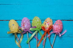 Easter background. Multicolored decorated easter eggs, multi-colored powder on a turquoise background. Free space Stock Image