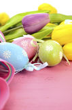 Easter background with painted Easter eggs, yellow and purple silk tulips Stock Images