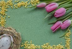 Easter background with pink tulips and egg on green glitter background with copy space royalty free stock photo