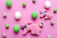 Top view of Easter eggs and rabbits on a pastel pink background. Easter background is an punchy pink color with a variety of Easter eggs and funny rabbits. Top Royalty Free Stock Images