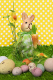 Easter background with a rabbit. An Easter background with a rabbit and realistic looking chocolate eggs on polka dot texture Stock Photo