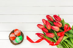 Easter background. Red tulips and Easter eggs on white wooden background Royalty Free Stock Photography