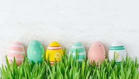 Easter background with row of colorful eggs hiding in  green gra. Ss, copy space. Top view.  Easter holiday decorations Royalty Free Stock Image