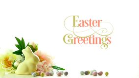 Easter background with white chocolate bunny and spring flowers border and text. Easter theme background with white chocolate bunny, eggs and spring flowers stock photography