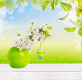 Easter background with white wooden table, deco eggs and vase with cherry blossom Stock Images