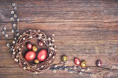 Easter background. Easter willow wreath and colorful Easter eggs on old wooden background. Top view, copy space, toned. Greeting card Stock Photography
