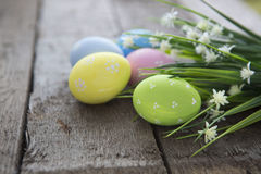Easter Background With Colorful Eggs And Flowers Over Wood. Stock Photo