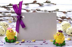 Easter Background with yellow easter eggs willow branches purple ribbon and little chickens space for text. Royalty Free Stock Photo