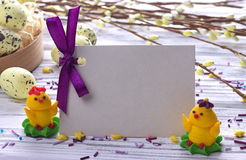Easter Background with yellow easter eggs pussy willow branches purple ribbon and little chickens space for text. Stock Images