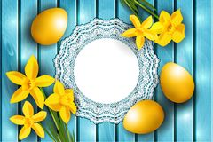 Easter background, yellow eggs and narcissus laying on blue wooden board Stock Photo