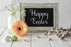Easter background. Yellow herbera and pussy-willow flowers aroun. D blackboard in matching frame. Text `Happy Easter!` on a blackboard Stock Images