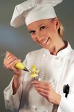 Easter Baker. Happy female Baker piping a daffodil flower Stock Photos