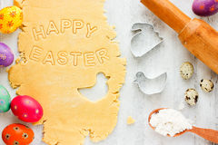 Easter baking concept: raw dough for biscuit, colorful eggs Royalty Free Stock Photos