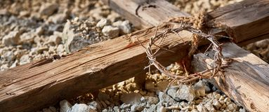 Easter banner commemorating the Crucifixion. With a close up view of a wooden cross on stony ground with a bloodstained crown of thorns stock image