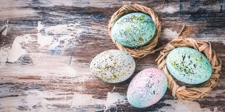 Easter banner. Easter eggs in nests. Rustic surface. Vertical shot royalty free stock images