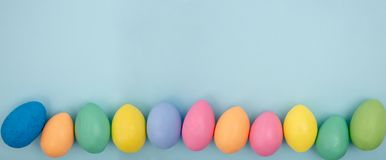 Easter banner. Frame with colored hand made eggs. View from the top. Spring easter border made with candy colored eggs on pastel pink background. Banner. Copy royalty free stock photography