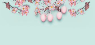 Easter banner with hanging pastel pink Easter eggs and spring blossom at light at blue turquoise background Stock Photos