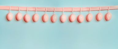 Easter banner or template. Beautiful pastel pink eggs hanging on ribbon at at blue turquoise background. Front view, copy space for greeting or invitation royalty free stock photo