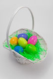 Easter Basket. An Easter Basket containing colorful plastic Easter eggs with green grass. The object is isolated on a gray background Royalty Free Stock Photos