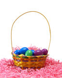 Easter Basket. A Easter basket filled with eggs on some pink paper shreds Stock Image