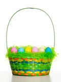 Easter Basket. With colored eggs, white background, vertical stock photography