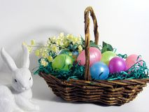 Easter Basket. Filled with colorful eggs, yellow flowers and white ceramic rabbit royalty free stock photos
