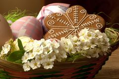 Easter basket with beautiful white flowers. Basket with colored eggs, flowers and gingerbread Stock Image