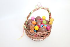 Easter basket chocolate eggs flowers Stock Photography