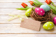 Easter basket. With colored eggs and handwritten Frohe Ostern! over wooden background Royalty Free Stock Photography