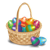 Easter basket with colored eggs on a white background Royalty Free Stock Photos