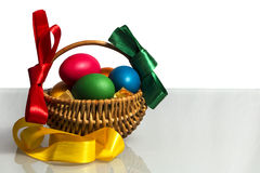 Easter basket with colored ribbons in the middle of 2 backgrounds. Easter Wicker basket with pink vines painted chicken eggs on a white background and on the royalty free stock image
