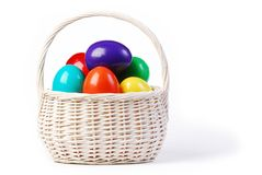 Easter basket with colorful eggs. White washed wicker basket full with large colourful eggs Stock Photo