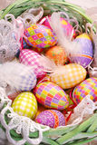 Easter basket with colorful eggs and feathers Royalty Free Stock Image