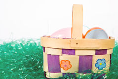 Easter basket wih colorful eggs. An Easter basket with colorful eggs sitting on fake green grass Royalty Free Stock Photography