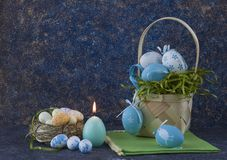 Easter basket with coloured Easter eggs on dark stone table stock image