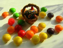 Easter basket with decorative eggs and a cupcake. Colored candy is scattered around Stock Images