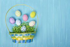 Easter basket and eggs on a blue background Royalty Free Stock Image