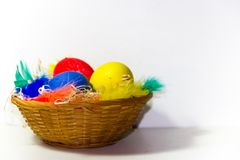 Easter basket with eggs and colorful feathers on white background. Colored easter eggs and nests with colored feathers royalty free stock photos