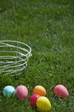 Easter - Basket and Eggs Detail. A white basket and colorful Easter eggs laying around on the green grass Stock Images