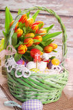 Easter basket with eggs and fresh tulips Royalty Free Stock Images