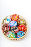 Easter basket with eggs isolated. Easter basket with several hand painted egss isolated Stock Photo