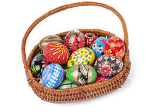 Easter basket with eggs isolated. Easter basket with several hand painted eggs isolated Royalty Free Stock Images