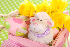 Easter basket with eggs and sheep figurine. Pink easter basket with eggs and funny sheep figurine on green dotted background stock images