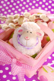 Easter basket with eggs and sheep figurine. Pink easter basket with eggs and funny sheep figurine on purple dotted background royalty free stock photo